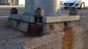 Signs of rust and discoloration at the bases of the bridge light towers.