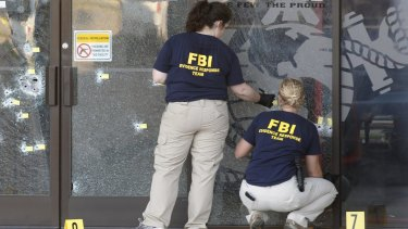 FBI agents gather evidence at the Armed Forces Career Centre in Chattanooga, Tennessee.
