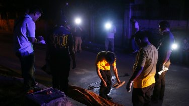 Funeral workers prepare to remove the body of a crime suspect after he was killed in gunbattles late in Manila, Philippines.