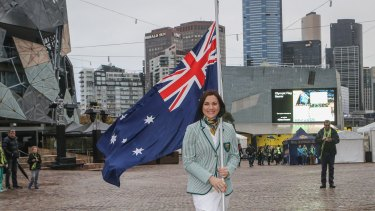 Anna Meares gets some practice for Rio, carrying the flag through Federation Square in Melbourne.