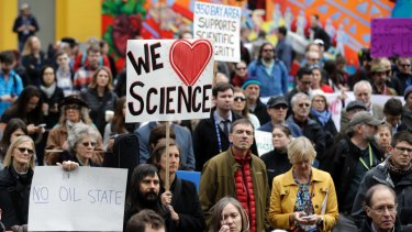 People hold signs as they listen to a group of scientists speak during a rally in conjunction with the American Geophysical Union's meeting in December.