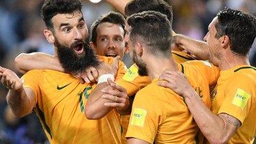 Triumphant return: Socceroos skipper Mile Jedinak is swamped by his teammates.