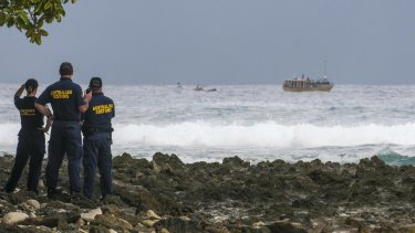 Customs officials watch a boat filled with asylum seekers approach the Cocos Islands in 2012.