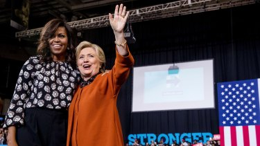 First lady Michelle Obama and Democratic presidential candidate Hillary Clinton stand on stage after speaking at a campaign rally at Wake Forest University in Winston-Salem, NC.