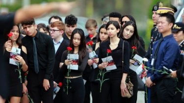 Mourners hold flowers during the funeral for Peter Wang.