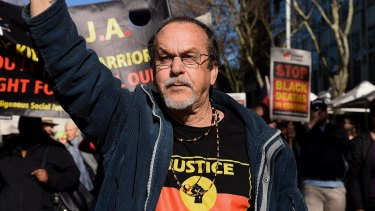 A protester marches on NSW Parliament House over Eric Whittaker's death.