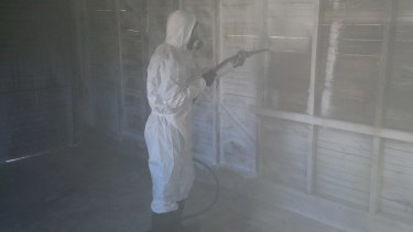A cleaner decontaminating a garage with chemical foam.