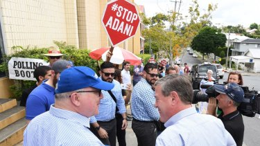 Attorney-General Georg Brandis and Queensland LNP leader Tim Nicholls with anti-Adani coal mine protesters during the recent state elections.