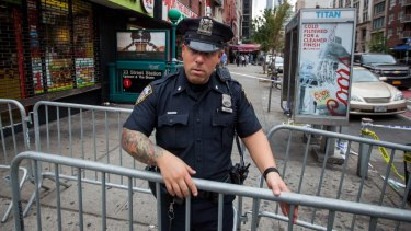 A New York City Police Department officer places barricades near the site of a bombing in 2016.