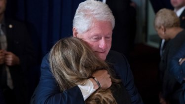 Former President Bill Clinton hugs a woman after his wife, Democratic presidential candidate Hillary Clinton spoke in New York on Wednesday.