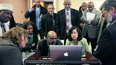 Muslim, Christian, minority and government leaders fix their eyes on a laptop screen showing a video as part of a federal pilot program called Countering Violent Extremism, at Roxbury Community College in Boston.
