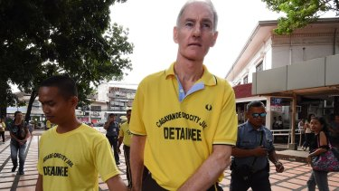 Peter Scully (right) arrives at the Cagayan De Oro court handcuffed to another inmate on his first day of his trial.