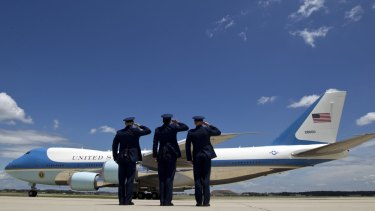 Military personnel salute as Air Force One, with President Barack Obama and Democratic presidential candidate Hillary Clinton aboard, departs Joint Base Andrews, Maryland, in July.