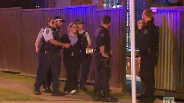 Police console a woman at the scene of the crime on Brisbane Street.