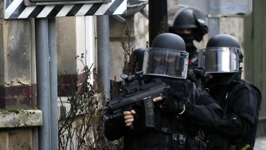 SWAT police officers on patrol in the village of Longpont, north-east of Paris, in search of the two heavily armed brothers suspected in the massacre at <i>Charlie Hebdo</i> magazine.