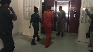 Australian nurse and surrogacy broker Tammy Davis-Charles, in orange, arrives in court in Phnom Penh on May 18.