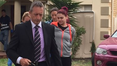 A woman is led away by Armed Crime Taskforce Detective Inspector Steve Clark after a raid in Point Cook.