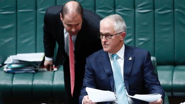 Environment and Energy Minister Josh Frydenberg whispers to Prime Minister Malcolm Turnbull in Parliament.