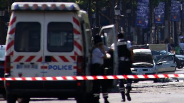 Police forces secure the area after a man rammed a police vehicle on the Champs Elysees in Paris, in June.