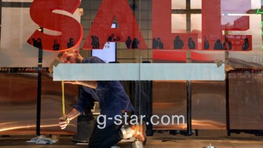 An employee places a sales sign in the window of a G-Star Raw Denim SL fashion retail store on Oxford Street.