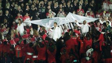 Ian Thorpe carries the Commonwealth Games flag.