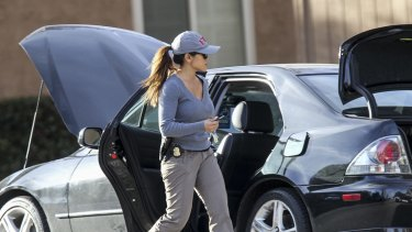 Searching for answers near and far: an FBI agent at a car being investigated by police.
