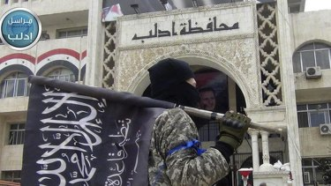This image posted on the Twitter page of the Nusra Front, al-Qaeda's Syrian arm, on Saturday shows a fighter carrying Nusra's flag in front of the governor's building in Idlib, northern Syria.