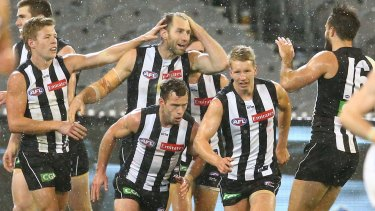 Travis Cloke and his Magpie teammates celebrate a goal in Friday night's win against Fremantle at the MCG.