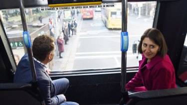 Gladys Berejiklian and Andrew Constance scope the view from the top seat of a double-decker bus