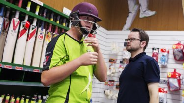 My size:  Nathan Simmons, 14, from Bankstown, having his helmet fitted by Stuart Aley of Kingsgrove Sports Centre.