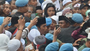 Indonesian President Joko Widodo, centre, is photographed as he joins the demonstrators on December 2.