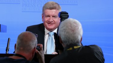 Behind the media scrum is Minister for Communications and Minister for the Arts Mitch Fifield
