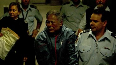 Philip Nguyen is led away by police after the shoot-out in September 2010 in which Constable Bill Crews was killed.