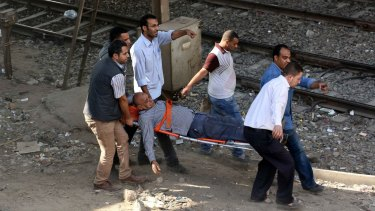 Wounded: Egyptian men carry an injured man on a stretcher after the bomb exploded on the metro.