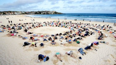 More than 400 people gather at Bondi Beach to bury their heads in the sand to send a climate change message to Prime Minister Tony Abbott during the G20 Summit in 2014.