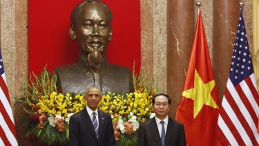 US President Barack Obama, left, stands next to Vietnamese President Tran Dai Quang under a bust of Vietnamese revolutionary leader Ho Chi Minh at the Presidential Palace in Hanoi on Monday.