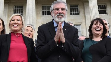 Sinn Fein president Gerry Adams, centre, bows to a group of Japanese tourists as he attends a press call alongside northern leader Michelle O'Neill, left, and Michelle Gildernew at Stormont.