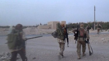 Islamic State militants carry weapons as they battle against Syrian government forces in Qaryatain in a photo released by Rased News Network on Facebook.