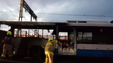 Firefighters sweep water away from a bus blackened by a fire on the Sydney Harbour Bridge.