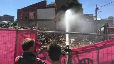 Firefighters dampening down building waste where Carlton's Corkman Irish Pub stood for 159 years.