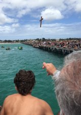 Father Eleftherios Tatsis tosses the cross into the water.