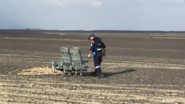 A Russian emergency worker examines damaged seats from the crashed plane.