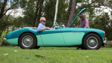 Frank Robson ponders the suspension of the Austin-Healey roadster while owner Paul Blake tinkers under the hood.