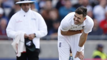 Umpire Aleem Dar looks on as England fast-bowler Jimmy Anderson grimaces due to injury.