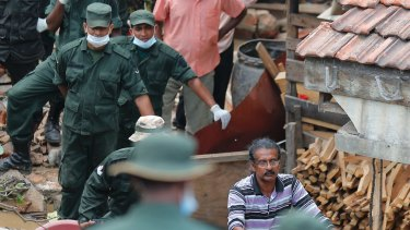 A Sri Lankan man helps military rescuers dig his buried house.