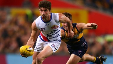 Tom Liberatore helps the Bulldogs to an elimination final win over West Coast last year. A last-round wildcard weekend could radically re-shape the first week of finals.