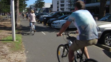 Bike riders on the shared pedestrian and cycle path along Manly Beach.