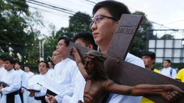 A Catholic priest carries a wooden crucifix during a prayer vigil held last month to protest against the killings in the Philippines as President Duterte pursues his war on drugs.