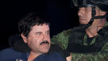 """Joaquin """"El Chapo"""" Guzman is made to face the media as he is escorted to a helicopter after his arrest."""