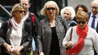 Liz Noble, left, the mother of Rozelle store explosion victim Chris Noble, arrives at court with supporters on Friday.